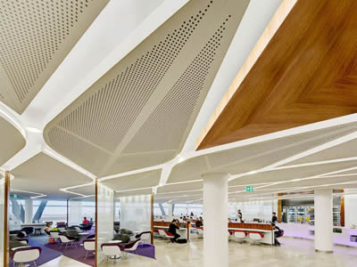 Leaf-shaped perforated metal ceiling with round holes is on the top of air waiting room.