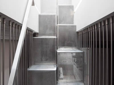 A perforated metal staircase features alternating treads with small holes in staggered rows.