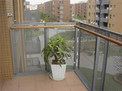 Perforated metal fences with square holes in straight rows are standing on the edges of balcony where there is a pot of flower.