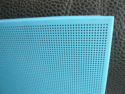 A piece of perforated metal ceiling with small round holes in straight rows and blue surface.