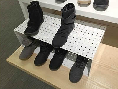A box-shaped perforated metal shoe display rack in white with round holes, and four shoes are in it which two shoes are on.