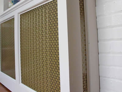Perforated brass sheets are installed on  the radiator cabinets as grilles.