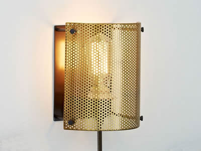 A perforated brass sheet is installed around the lighting area.