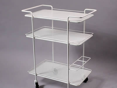 A perforated white metal serving cart with square holes in straight rows, three tiers and four black wheels.