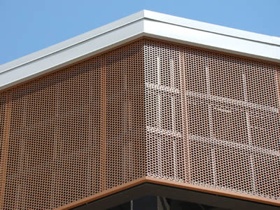 Several perforated copper sheets are installed on the building facade.