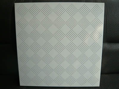 A piece of perforated metal ceiling sheet with small round holes arranged to diamond in straight rows.