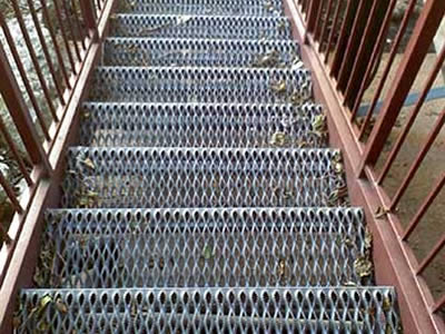 A non slip stair consists of diamond-strut stair treads and red fences.