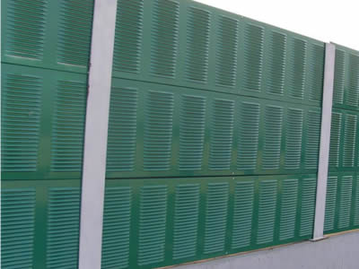 Noise barriers consist of green metal sheets with shutter holes in straight rows.