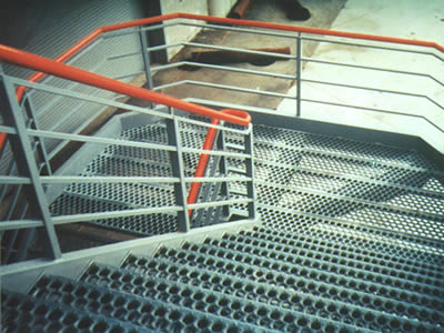 A non slip stair is mad of o-grip safety grating and metal fences whose tops are red.