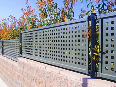 Perforated metal fences on the brick fences with square holes in straight rows are higher and higher from left to right.