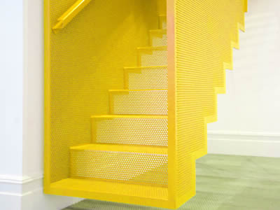 A perforated metal staircase with yellow surface and not touching the floor looks like hanging on the wall.