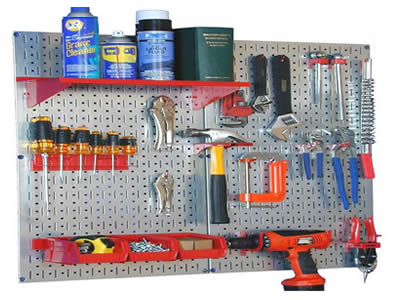 Many hardware metal tools are in the perforated metal pegboard display rack with combination of oval holes and slot holes.