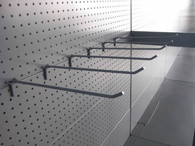 A perforated metal pegboard display rack  with a row of hooks, round holes in straight rows.