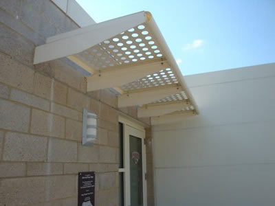 A horizontal perforated sunshade panel is installed above the door.