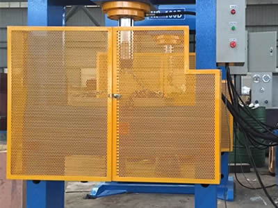 Two perforated machine guards with yellow surface and round holes in staggered is in the front of the machines, and the same two are in the behind.