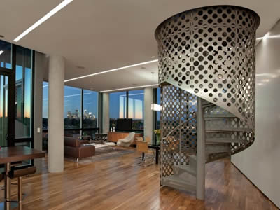 A perforated metal staircase with both treads and fences made of perforated metal is spiral indoors.