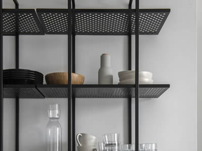 A black perforated metal display rack with cross holes in staggered holes, and tableware and dinner sets are on it.