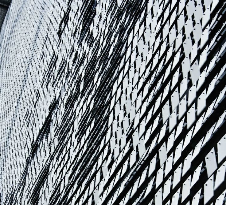 Many perforated plate screens are installed on large buildings walls and waving in wind.