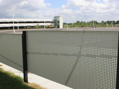 Perforated metal fence with square holes in straight and green surface are in the edges of lawn.