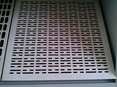 A perforated metal floor with long striped holes and two same shorter striped holes arranged across.