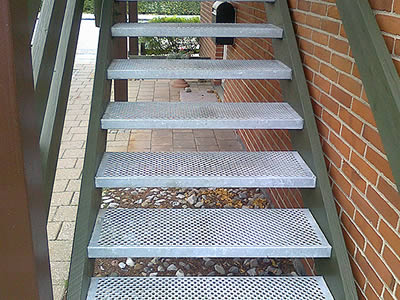 A traction-grip non slip stair is made of aluminum treads and green fences.