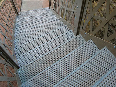 A perforated metal staircase with round holes treads and triangle hole fences is in outdoors.