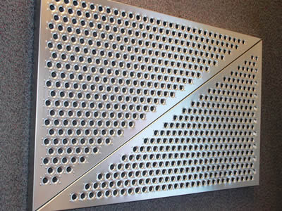 Two triangle perforated metal ceiling tiles with round holes in staggered rows sounded by convex starting points.