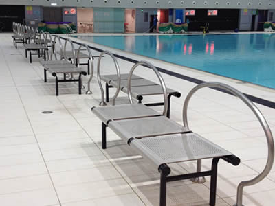 Many perforated metal chairs in staggered rows with slotted holes is beside the swimming pool.