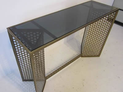 A console table consists of black transparent glass tabletop and perforated metal with round holes in staggered rows.