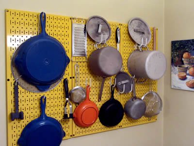 A yellow pin-up perforated metal display rack with combination of round holes and slotted holes, and many cookers are hanging on it.