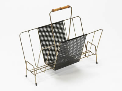 A magazine perforated metal display rack consists of black perforated metal shelf with square holes and galvanized metal supports.