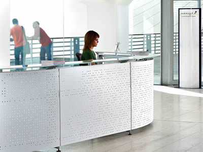 A reception desk consists of transparent glass and perforated metal with square holes and white surface.