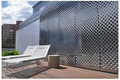 Perforated screen is installed on the wall and two lounge chair and a round stool is on the ground.