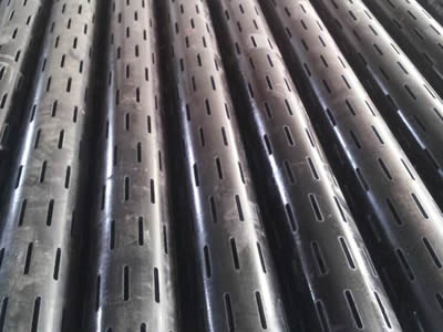 Many perforated pipes with slotted holes on the ground.