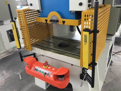 Two perforated machine guards with yellow surface and slotted                holes in straight rows are equipped in left and right of the press.