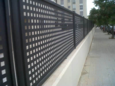 Perforated metal fences with black surface and square holes in straight rows are on the cement fence foundation.