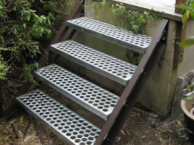 A non slip stair with silver O-grip stair treads mounted to black stringers is used in residential zones to keep walkers safe.