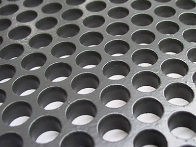 A piece of perforated vibrating screen with round holes in staggered rows.