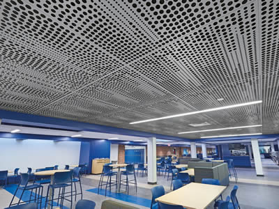 Perforated metal ceiling with round holes of different sizes is on the top of the classroom.
