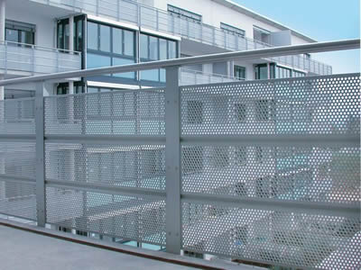 Perforated metal fences with round holes in staggered rows are behind the railings.