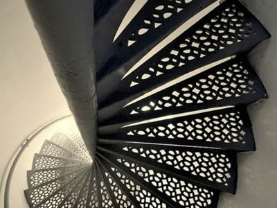A spiral perforated metal staircase with special hole treads is black.
