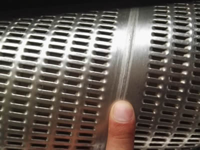 Spiral lock seam perforated filter pipe touched by a finger.