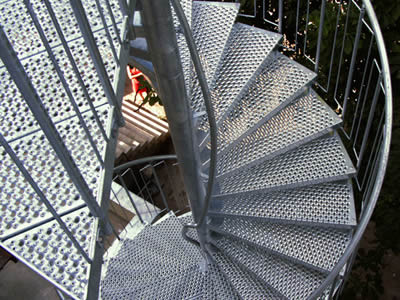 A spiral perforated metal staircase treads with bigger round holes surround by smaller round holes.
