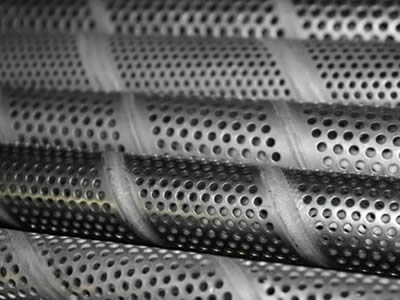 A row of spiral welded perforated pipes with round holes in staggered rows.