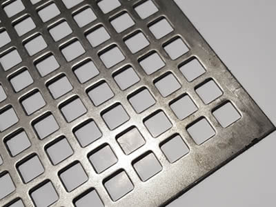 A piece of perforated vibrating screen with square holes in straight rows.