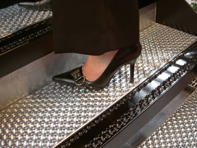 A woman is walking on the traction-grip non slip stair with silver treads mounted to black metal stringers.