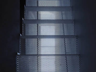 A straight perforated metal staircase with round hole treads.