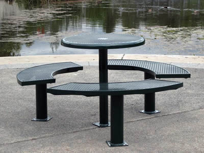 A set of tables and benches with round holes and green surface is round beside the pond.